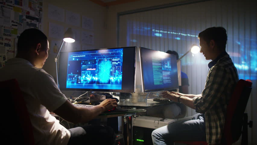 4K Young creative computer design team working together in dark office.