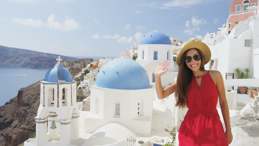 Excited young woman waving hello at village Oia, Santorini, Greece, Europe. Young tourist is visiting famous landmark tourist destinations wearing sunhat, sunglasses and red dress. SLOW MOTION.   Shutterstock HD Video #15325087