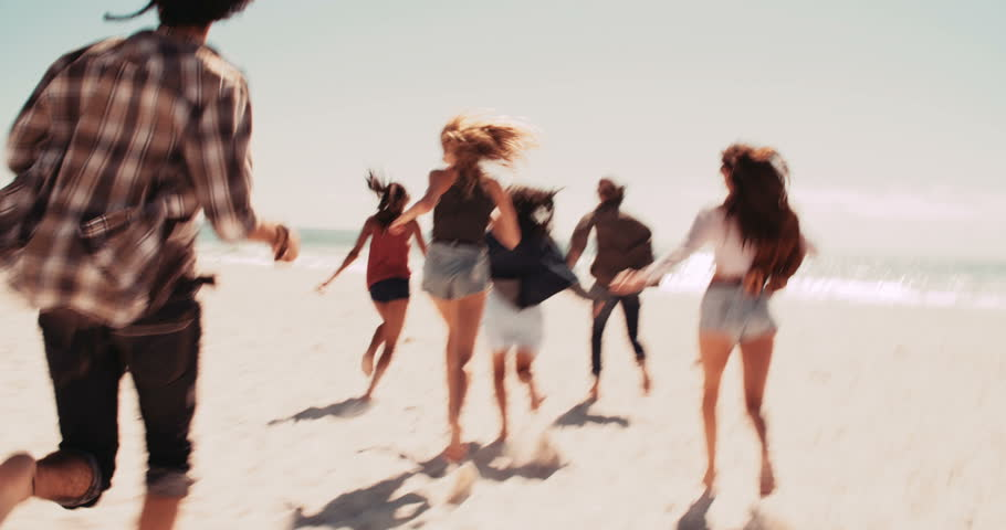 Multi-Ethnic group of road trip friends jumping out of retro van barefoot and running at sunny sandy beach