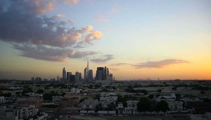 Afterglow to darkness sky time lapse. Light dark clouds over Dubai skyline. Aerial view, flat urban area ahead, pack of tall towers seen far afield, Dubai Downtown and skyscrapers around Sheikh Zayed #15338230