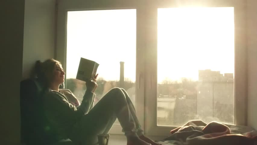 Beautiful young woman sitting on window sill with coffee end reading book on background of sunset | Shutterstock HD Video #15359080