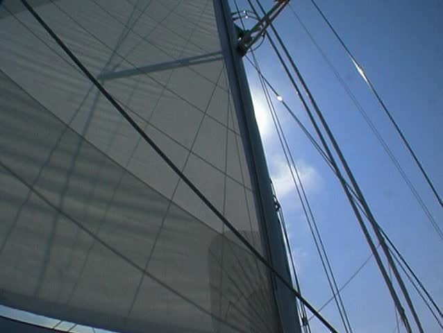 Yacht at sea, sails and sun, pan to cockpit