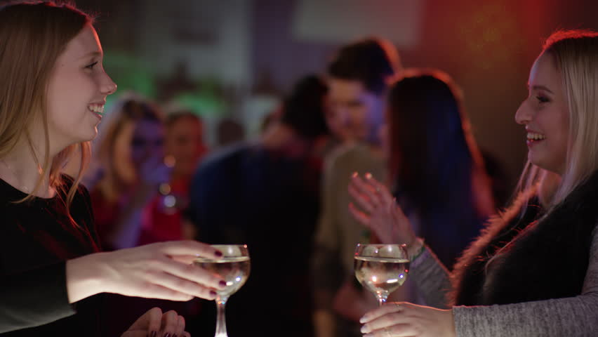 Two attractive girls at bar in club doing high five | Shutterstock HD Video #15369547