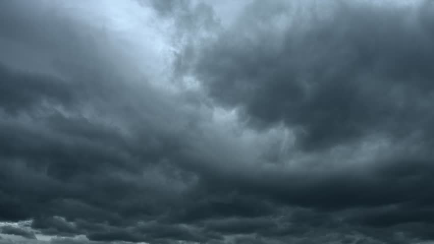 Heavy storm clouds in deep shades of gray. drifting slowly across the sky as lighting bolts streak downward. Video 4k