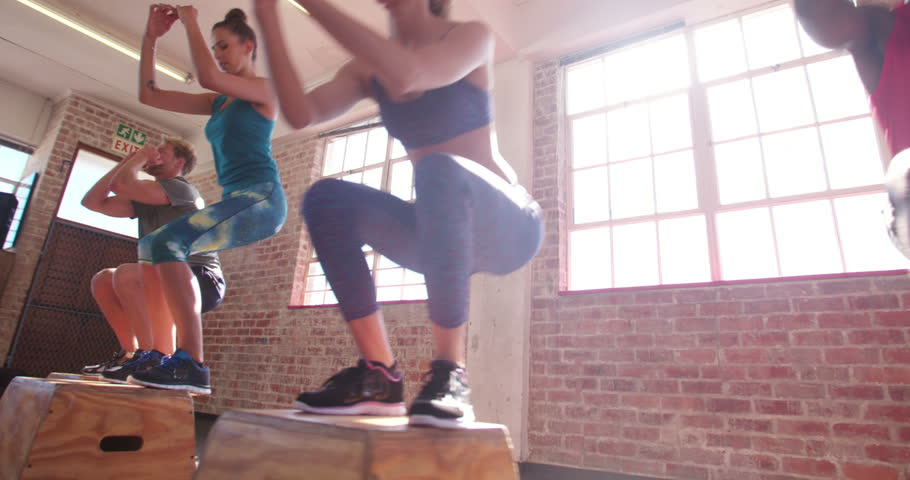 Multi-ethnic group of friends jumping onto wooden boxes in a crossfit training