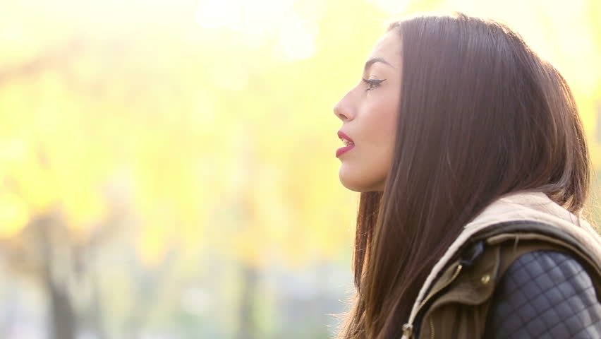 Close-up profile of a young beautiful brunette woman singing, graded   Shutterstock HD Video #15397633