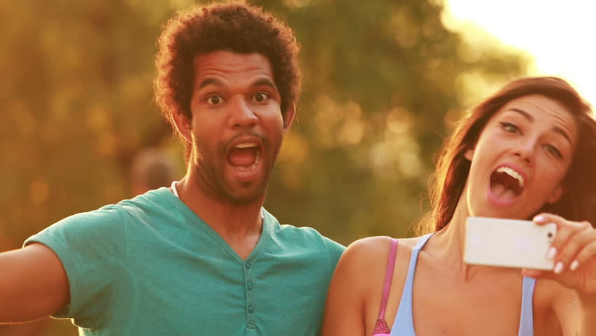 Close up of a young multi-ethnic couple having fun goofing around and making funny faces while taking a selfie at sunset, graded warmer.