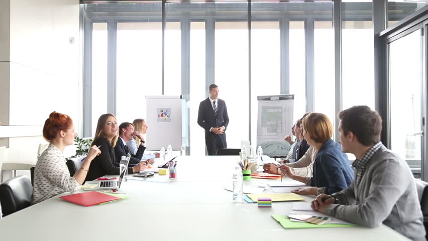 Handsome young director pointing at flipchart during a meeting | Shutterstock HD Video #15414625