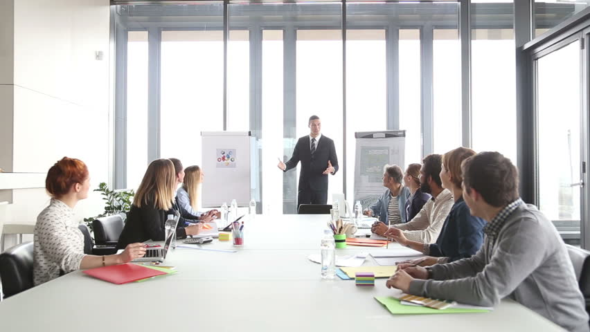 Handsome young director giving presentation to colleagues in conference room | Shutterstock HD Video #15414799