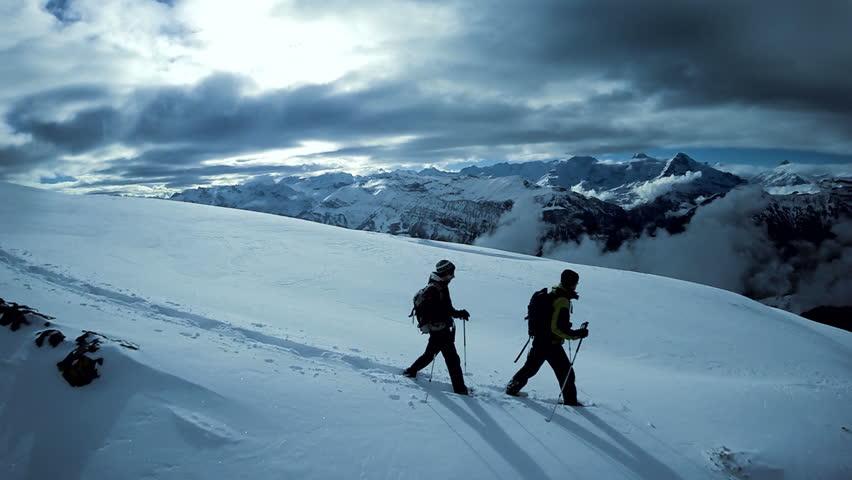 Two hikers walking on top of snow mountain peak. winter hiking journey adventure background | Shutterstock HD Video #15426940