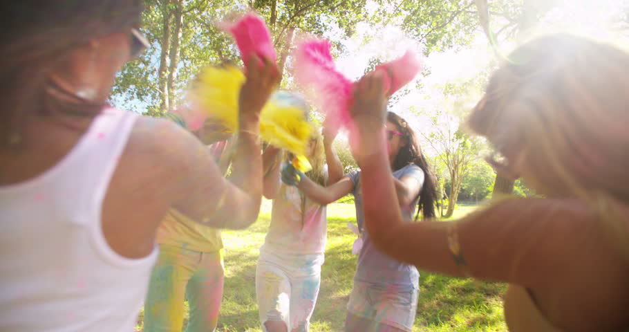 Friends throwing Holi powder at each other at a Holi Festival in a park in the daytime