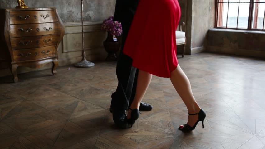 Legs of girl and man in black dancing tango in retro room