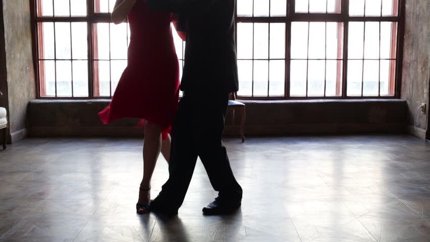 Legs of woman in red and man in black dancing tango near window