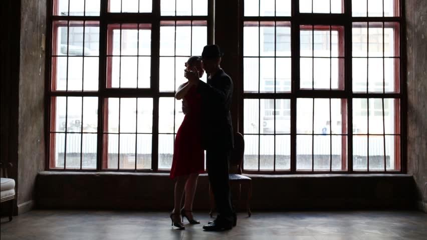 Woman in red dress and man in black suit dance tango near window