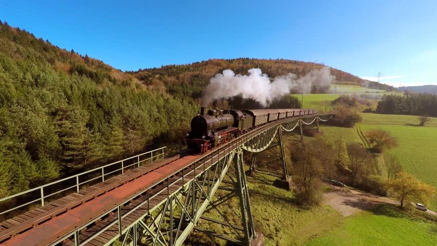 Nostalgic steam engine locomotive crossing bridge at sunset. old historical train technology background