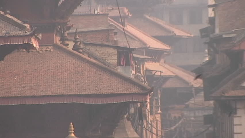 Zoom out to WS of people walking in old city of Patan, Nepal