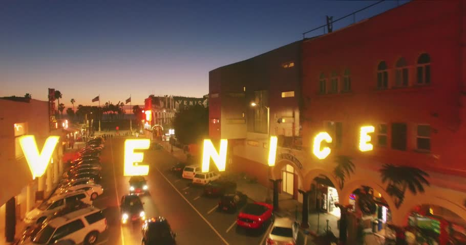 LOS ANGELES - Circa 2015: Closeup aerial view of iconic Venice sign, revealing Venice Beach boardwalk and Pacific Ocean at sunset. 4K UHD.