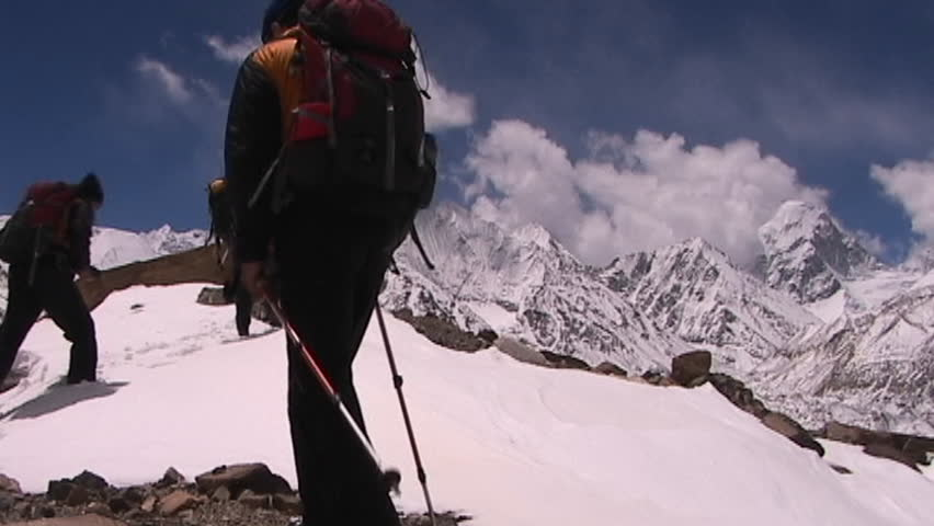 Climbers near Mt. Everest in Tibet walking over a snow hill with Mt. Pumori in the background
