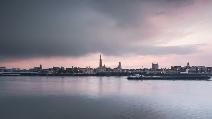 timelapse of antwerp city skyline at sunset from day to night