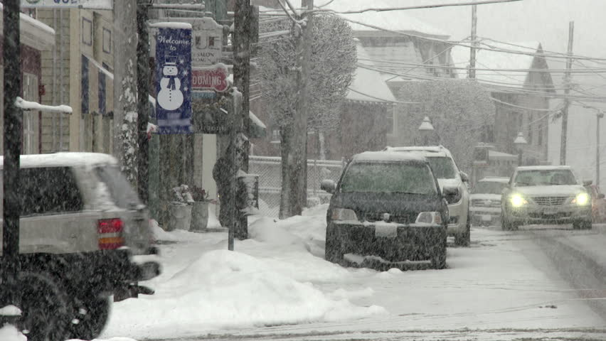 Traffic and parked cars during snow storm on small town street. 4K.