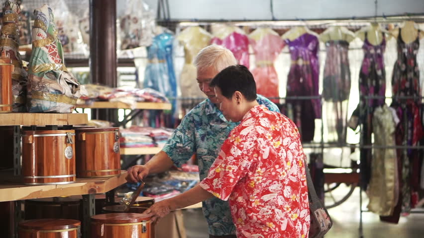 Asian senior elder tourist walking and shopping for local craft in Thailand