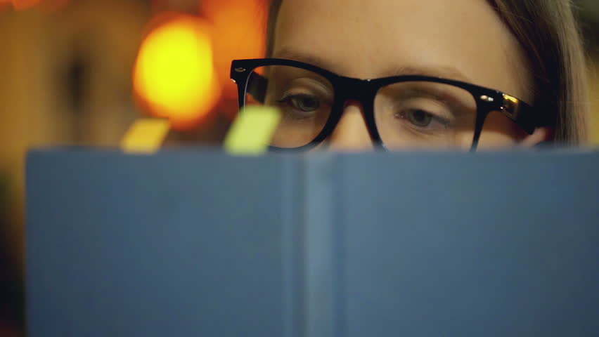 Girl wearing glasses and reading book in the cafe  | Shutterstock HD Video #15491143