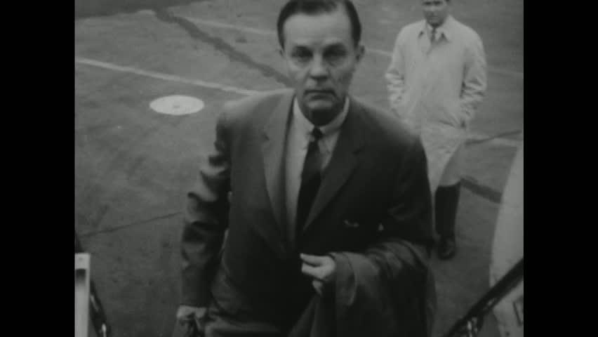 UNITED STATES 1950s: Senator Joseph Clark walks up steps to plane, toward camera / Clark in plane next to window.