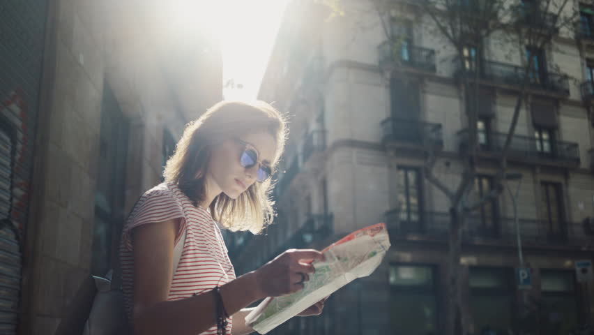 Young tourist woman exploring Barcelona map while traveling in Spain, vacation concept, flare light #15513184