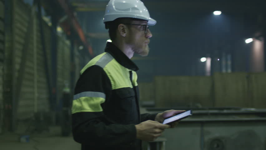 Engineer in hardhat is moving through a heavy industry factory with a tablet computer. Shot on RED Cinema Camera.