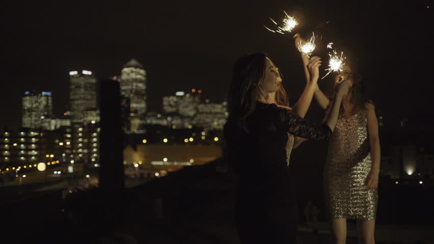 Female Friends party on rooftop at night with sparklers