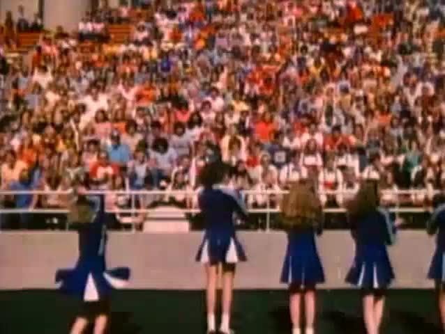 Cheerleaders facing spectators at high school football game, 1980s