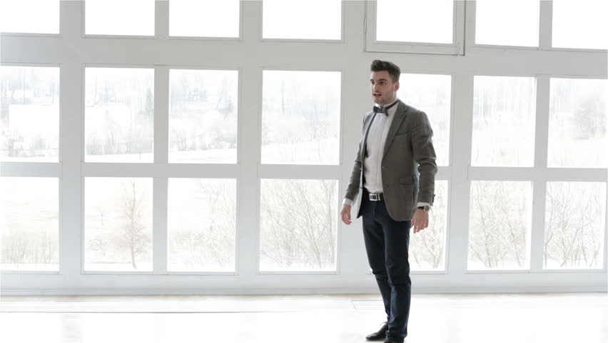 Businessman is rejoicing because of profitable deal. Attractive man in suit is happy. The man is jumping and waving his arms in delight. | Shutterstock HD Video #15550873