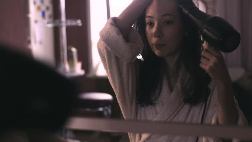 Girl in bathrobe dries hair a hairdryer | Shutterstock HD Video #15557353