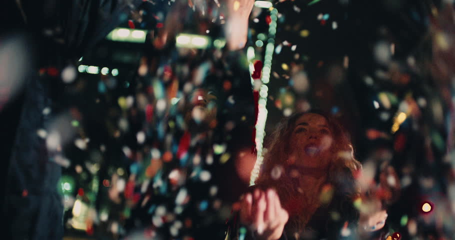 Teenager hipster friends celebrating a night party by blowing colourfull confetti with city lights in the background   Shutterstock HD Video #15559333