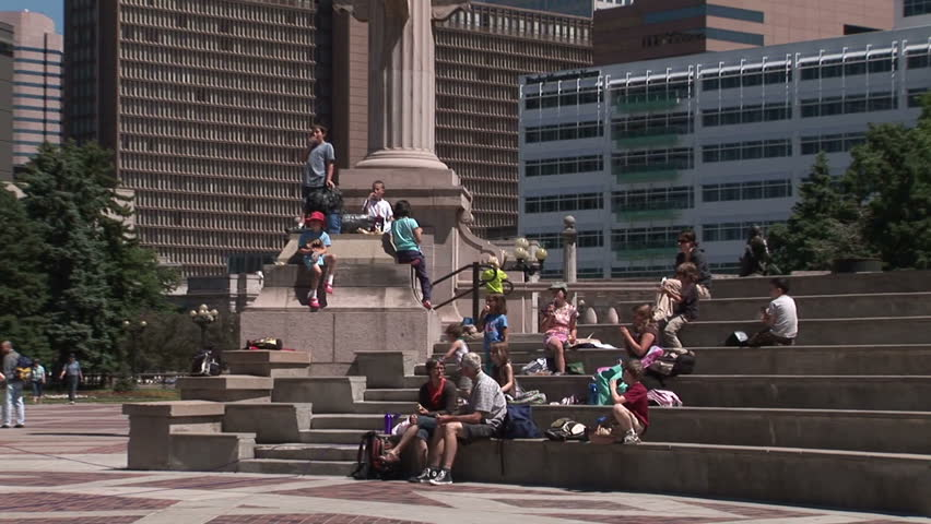 People taking in the sites of Downtown Denver from the stairs of Civic Center Park