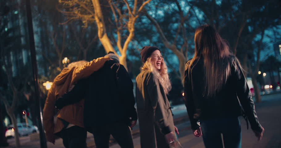 Young happy couples in winter outfits embracing while taking a night walk outside in the city #15559708