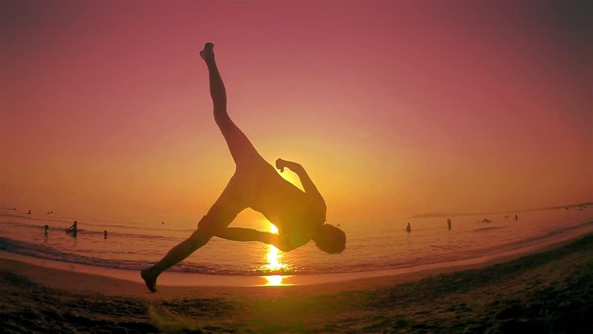 Parkour free runner runs and jumps back flip at summer beach sunset. Steadicam SLOW MOTION shot
