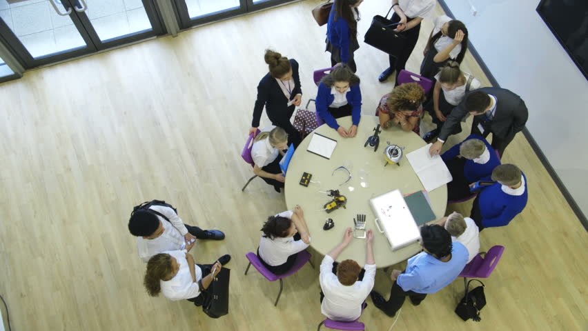 View from above of students and teachers in a technology lesson. Some are sitting at the table whilst others are standing and talking amongst themselves. | Shutterstock HD Video #15582913