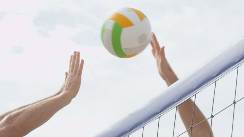 Beach volleyball net closeup spike and block. Man spiking smash and male player with unsuccessful blocking. People playing volley ball game exercising living healthy sports lifestyle. SLOW MOTION.