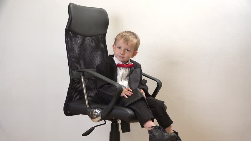 Cute Little Boy Sitting On Chair Stock Photo - Image of