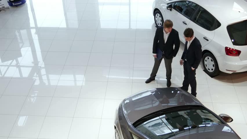 Salesman helping customer to choose a car