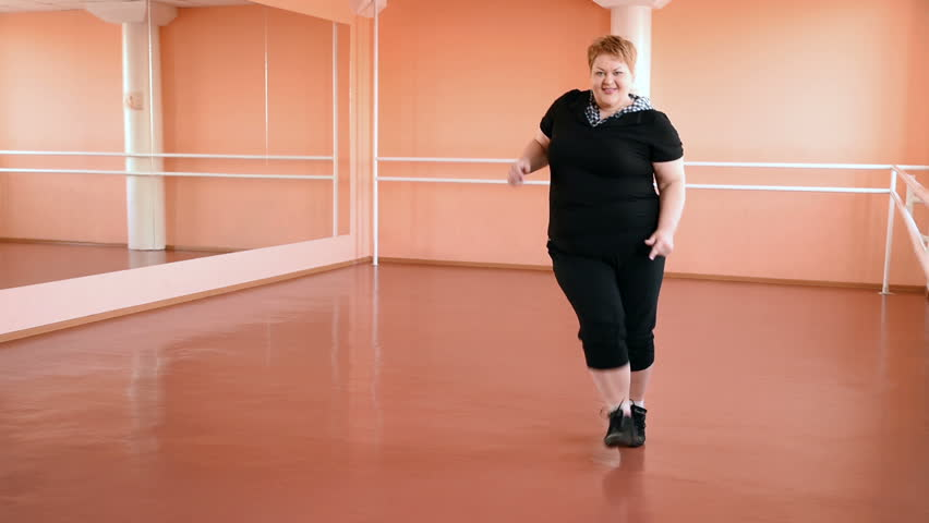 Heavy girl is engaged in dances in the hall. cheerful plump, gymnastics and dance