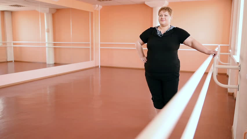 overweight girl is engaged in dances in the hall. cheerful plump, gymnastics and dance #15611143
