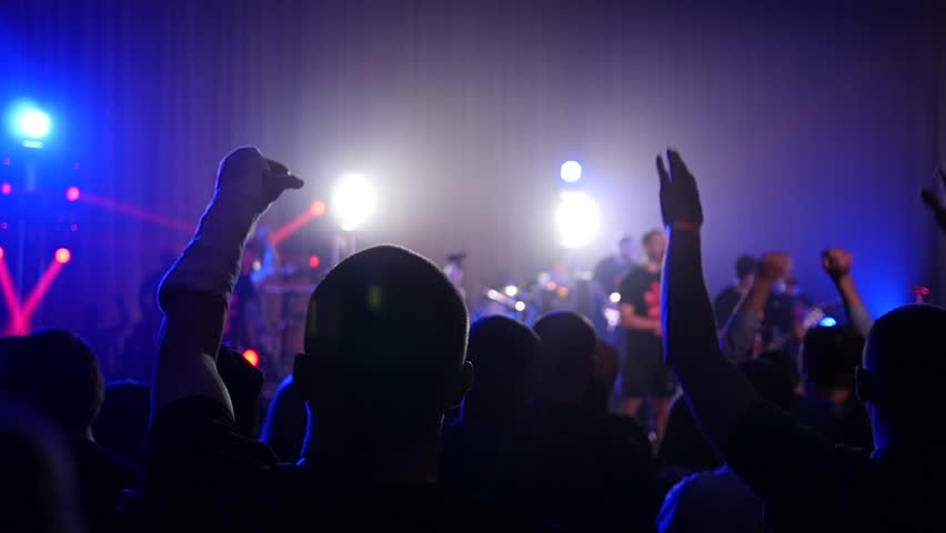KHERSON, UKRAINE - MAR 26, 2016 - Free public music concert - Cheering silhouettes crowd fan spectators rais hands up in air enjoying concert | Shutterstock HD Video #15623071