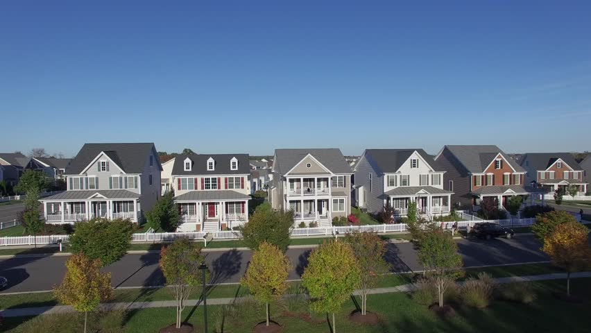 An aerial establishing shot of a suburban neighborhood, 4K UHD