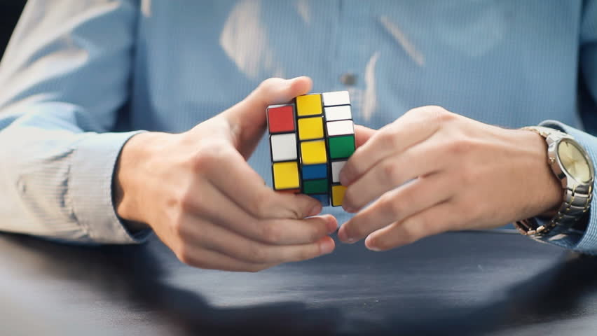 NEW YORK - APRIL 2: Businessman hands solving Rubik's cube puzzle on April 2, 2016. Rubics cube is the world's top-selling puzzle game and one of the world's best-selling toys.