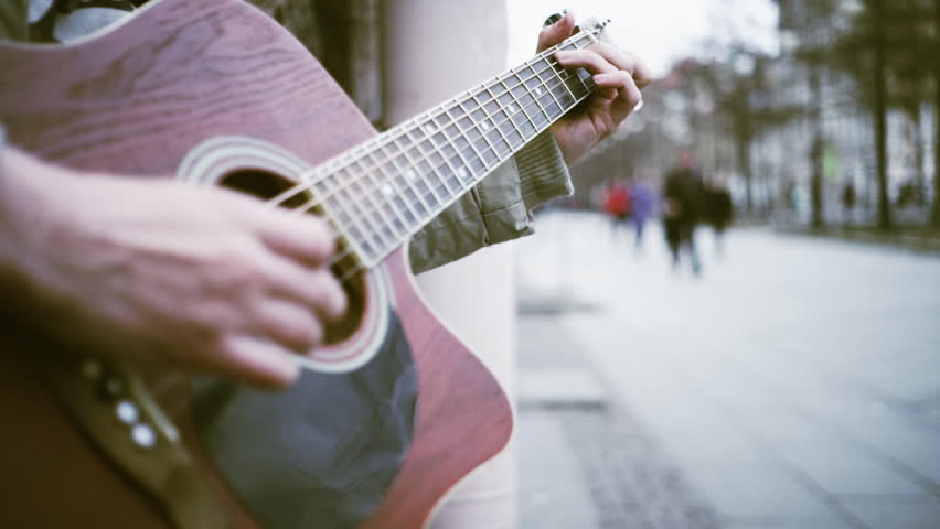 A man plays guitar on the street