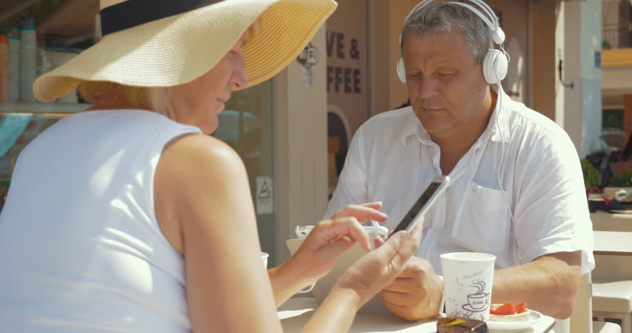 Senior family couple in street cafe on sunny summer day. Man in headphones listening to music or watching movie on pad while woman using smartphone