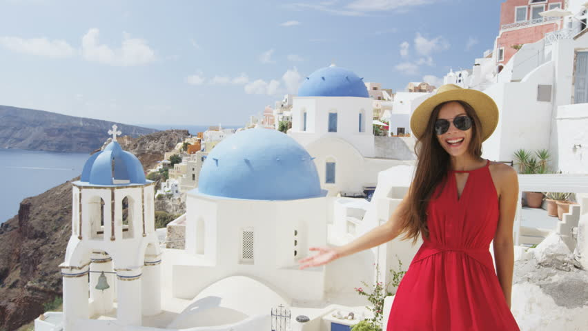 Woman with presenting showing welcome gesture in Oia Santorini, Greece, Europe. Young tourist is visiting famous landmark tourist destination wearing sunhat, sunglasses and red dress. SLOW MOTION.   Shutterstock HD Video #15646855