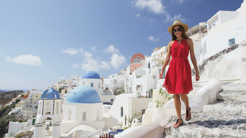 Tourist woman on travel walking on steps in Oia, Santorini, Greek Islands, Greece, Europe. Asian on travel enjoying vacation visiting famous tourist attraction destination, blue Domes on church.   Shutterstock HD Video #15647017